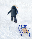 Little child pulling a blue sled on the snow Stock Images