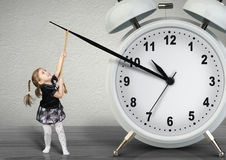 Little child pulling hand clock, time management concept royalty free stock photos
