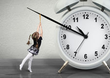 Little child pulling hand clock, time management concept Royalty Free Stock Image