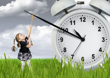 Little child pulling hand clock, time stop concept Stock Photo