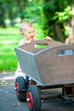 Little child push old wagon trolley Stock Images