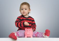Little child is putting coins in piggy bank and is saving money for future Stock Photo
