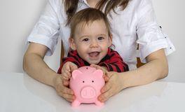 Little child is putting coins in piggy money bank Royalty Free Stock Photo
