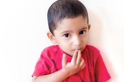 little child putting finger on mouth with small hairs Royalty Free Stock Image