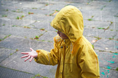 Little child in raincoat playing with raindrops Stock Photos