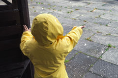 Little child in raincoat playing with water drops Royalty Free Stock Photography