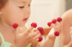 Little child with raspberry on fingers Stock Photo