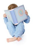 Little child reading book. Hiding behind book. Legs crossed. Over white background Stock Photos