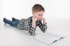 Little child reading book lying down. Stock Photos
