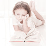 Little child reading book  lying down Royalty Free Stock Photos