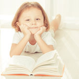 Little child reading book  lying down Royalty Free Stock Images