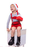 Little child in red costume of dwarf holding gift box with ribbon and looking up. Christmas Royalty Free Stock Photo