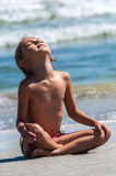 Girl yoga child relaxing beach ocean Royalty Free Stock Image