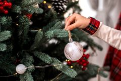 Little child`s hand decorating Christmas tree indoors. stock photos