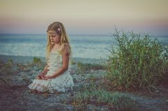 Sad girl with long blond hair sitting by the sea Royalty Free Stock Images