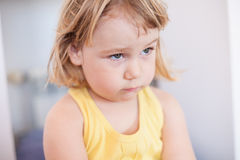 Little child sad face. Portrait of blonde two years old child with yellow shirt looking with sad face stock image