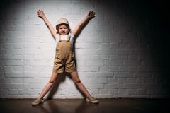 Little child in safari costume standing. At white wall royalty free stock images