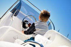 Little child sailor steering a sailboat as captain Royalty Free Stock Photography