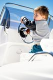 Little child sailor steering a sailboat as captain Stock Photos
