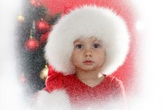Little child in Santa cap with Christmas tree on window looking at the winter. Kid and snowfall. Little child in Santa cap sitting by the window and looking at stock images
