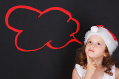Little child in Santa hat with dreaming couds. Stock Photos