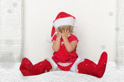 Little child in Santa suit sitting on floor with snow Stock Photography