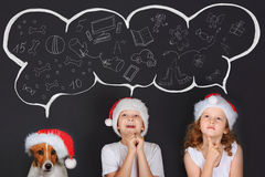 Little child in Sante hat, dreaming of the magic Christmas gifts. Little children and his puppy friend in Sante hat, dreaming of the magic Christmas gifts. Merry Stock Photography