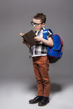 Little child with school bag and book in studio Stock Photography