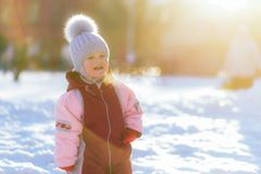 Little child screams outdoors in winter against sunset background. Little kid plays in the street in winter Stock Image