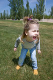Little child shouting in park. Three years old blonde child, with pigtail and blue jeans, standing and shouting in green grass in public park named Juan Carlos Stock Photo