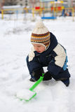 Little child with shovel and snow Royalty Free Stock Photos