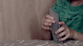 Little child shuffling cards. On the bed while playing in his room at home stock video footage