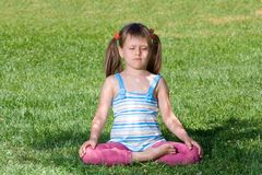 Little child sit and meditate in asana on grass Royalty Free Stock Images