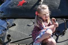 A little girl sits and is afraid of a Russian iron tank stock photos