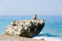 Young blonde boy sits on a huge coastal rock next to the blue sea, Greece. royalty free stock photos