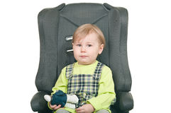 Little child sits in a car seat Stock Images