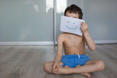 A little child sits on a floor with a smile. A little child sits on a floor and hold a white blank with a smile Stock Images