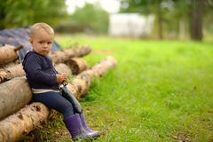 Little child sits on logs in village. Russian rural view Royalty Free Stock Photo