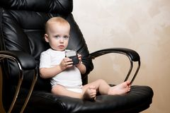 Little child sits in an office chair with a text stamp in his hands
