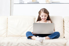 Little child sits on the sofa with laptop Royalty Free Stock Photography