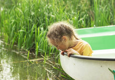 Little child sitting at the boat by a lake on summer day. Stock Images