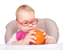 Little child sitting in a chair and plays with orange fruit Stock Photos