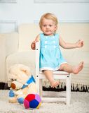 Little child is sitting on the chair Stock Photos