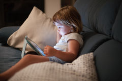 Little child sitting comfortably in sofa watching tablet Royalty Free Stock Photo
