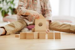 Little child sitting on the floor. Pretty boy palying with wooden cubes at home stock image