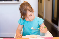 Little child sitting in high-chair eating cake with spoon Royalty Free Stock Images