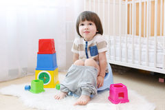Little child sitting on potty at home. Lovely little 2 years boy sitting on potty at home royalty free stock photos