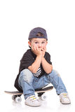 Little child sitting on a skateboard. Isolated on white background Stock Photo
