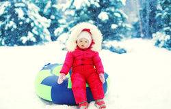 Little child sitting on sled in winter. Snowy day Stock Photo