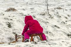 Little child sitting on a sleigh in the snow stock photography